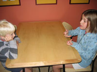 Two children sitting at a table and talking.