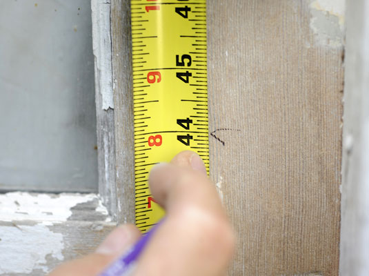 Using a tape measure to mark a position on a door.