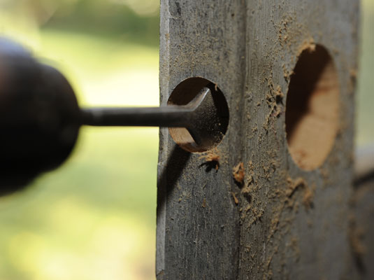 A drill, with a 1-inch spade bit, cuts the latchbolt hole into the door.