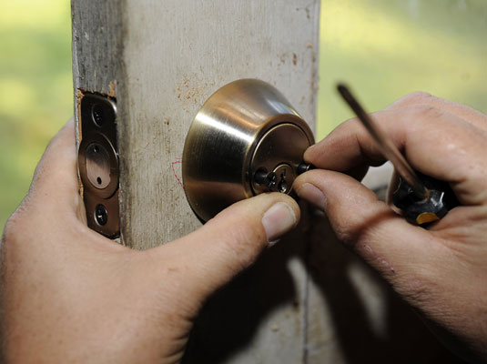 Installing the screws of the deadbolt.