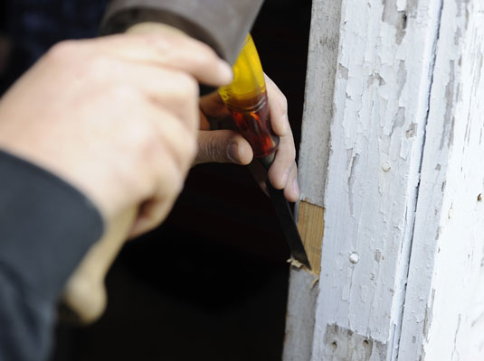 Using a chisel and hammer to cut a mortise on the doorjamb.