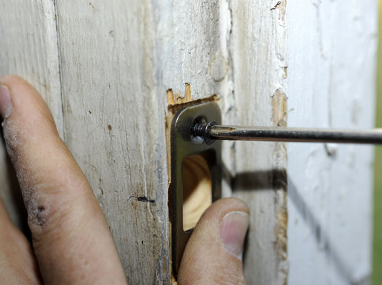 Installing a deadbolt's strike plate on a doorjamb.