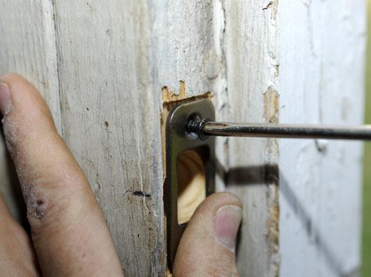 Installing a deadbolt's strike plate on a doorjamb.