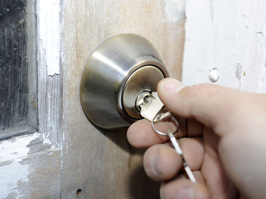 Unlocking a deadbolt lock to open a door.