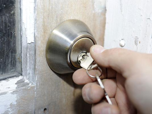 Unlocking a deadbolt lock to open a door.