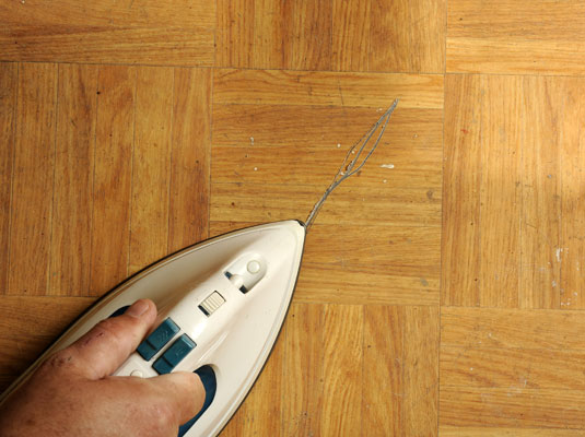 Use the iron to apply heat to the damaged tile and soften the adhesive.