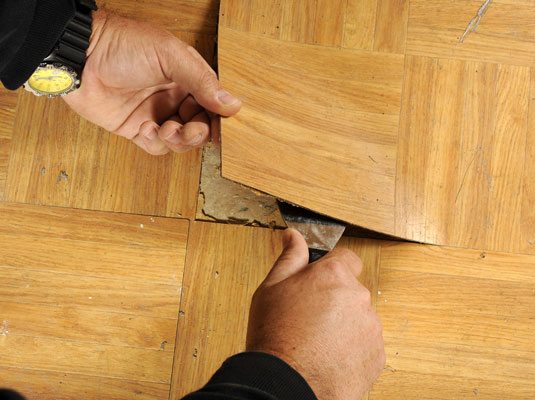 Lift the tile with the putty knife.