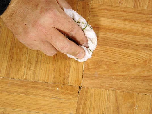 Wipe the tile to remove excess adhesive.