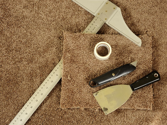 The tools needed to fix a damaged carpet: carpet remnant, carpet tape, tube of seam adhesive, putty knife, utility knife and a t-square.