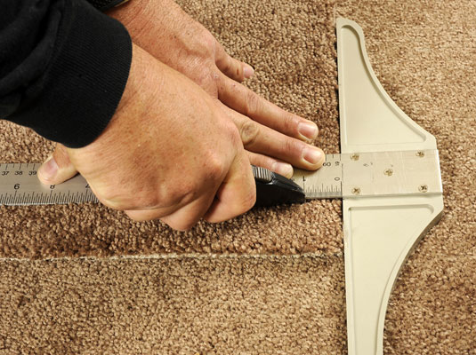 Cutting a piece of carpet with a utility knife and T-square.