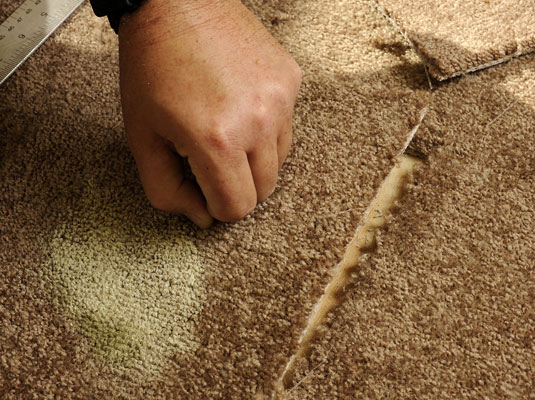 Removing a piece of carpet from the floor.