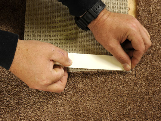 Applying seam adhesive to the edge of a carpet remnant.