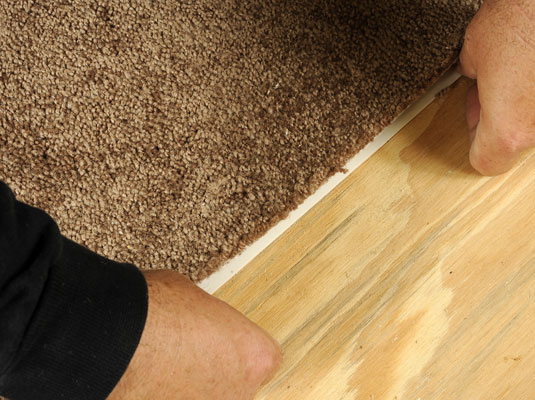 Apply the double-sided carpet tape to the outer edge of the hole in the carpet.