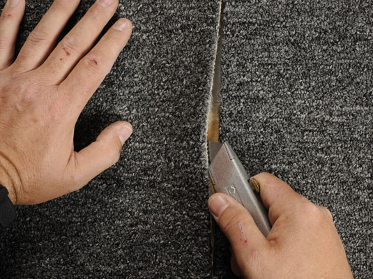 Using a utility knife to lift the edges of a ripped carpet.