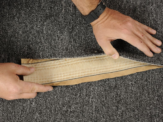 Shoving a piece of heat-activated carpet tape under a ripped carpet.