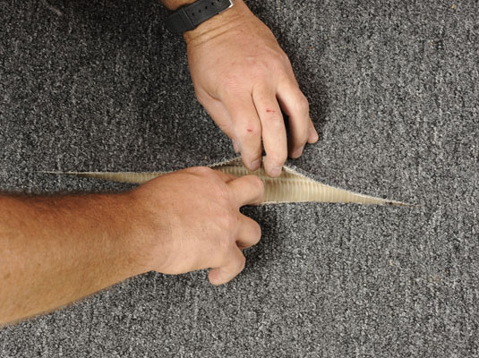 Laying the heat-activated tape into the seam of the carpet