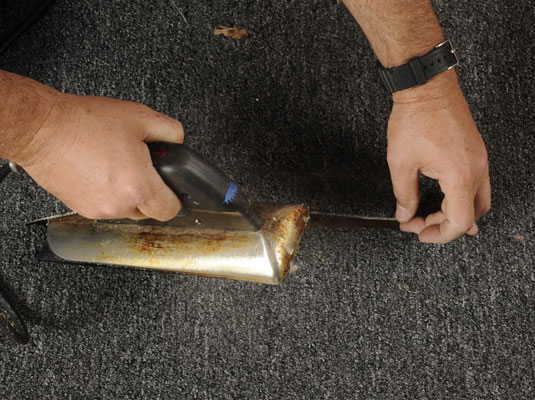 Removing a seam iron from the seam of a carpet.