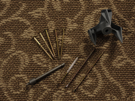 Materials needed to fix a squeaky carpeted floor: hammer, sticky notes or masking tape, drill, carpet repair kit.