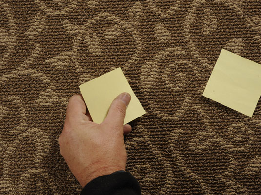 Man places sticky notes over a squeaky floor area.