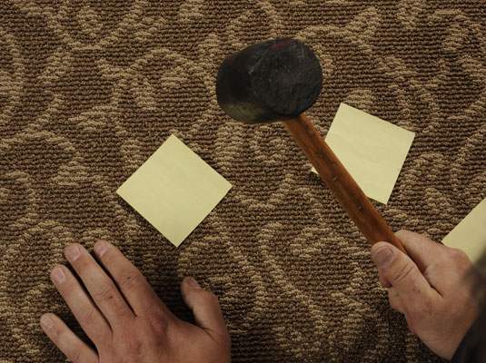 Using sticky notes as a reference, a man taps the squeaky floor with a hammer to locate the floor joist.