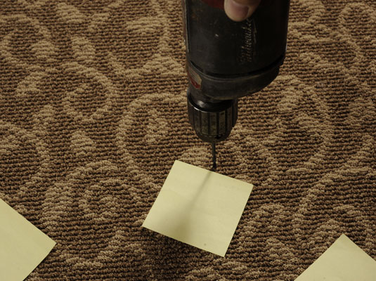 Using sticky notes as a reference, drill a test hole in the squeaky floor to find the joist.