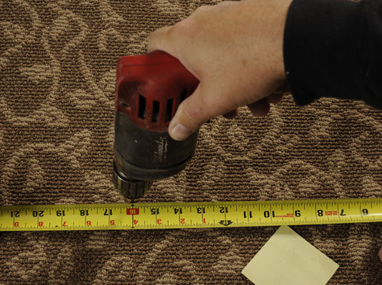 Person uses a drill and measuring tape to locate the joist on either side of the squeaky area of the floor.