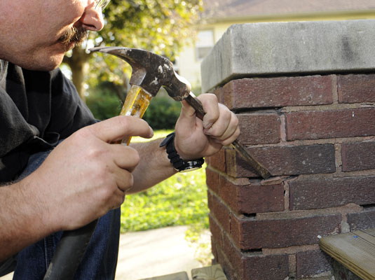 Man uses a chisel and hammer to remove any loose mortar in a brick wall.