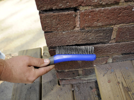 Man removes debris from a brick wall with a stiff brush.