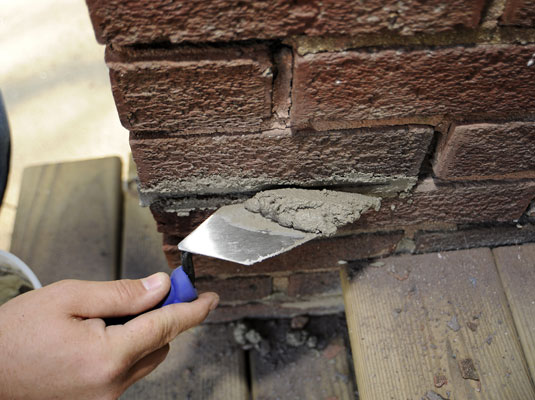 A man puts new mortar into the holes in a brick wall.