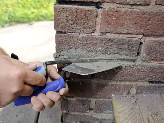 Man uses a pointed trowel to push the mortar in between the bricks.