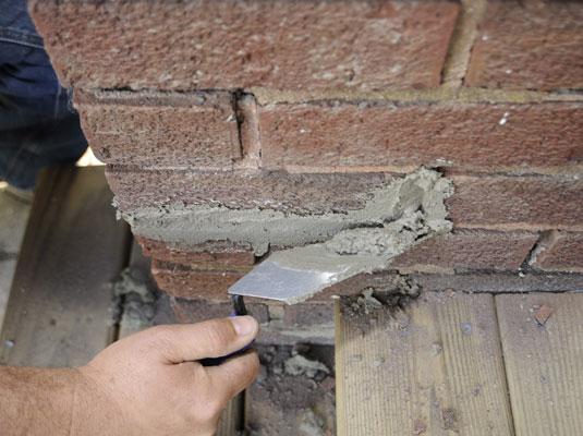 Person packs mortar into a brick wall.