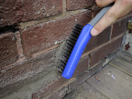Person scrubs a brick wall to clean it after applying mortar.