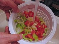 Rinsing vegetables under running water.