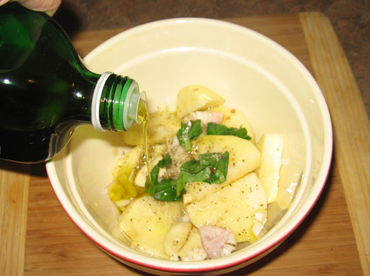 Adding olive oil to, and seasoning, a bowl of uncooked vegetables.