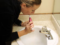Woman brushes her teeth.
